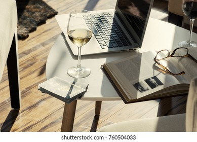 Modern wine bar cafe with computer, book and glasses of alcohol on table side angle view.