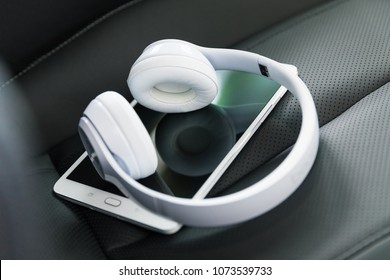 Modern wireless internet technology concept: macro view of tablet computer PC and white wireless headphones on the black leather car seat with selective focus effect