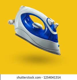 Modern wireless iron for ironing isolated on a yellow background. Levitation, minimalism. Photo with shadow
