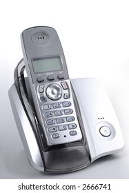 Modern wireless phone in cradle over gray background