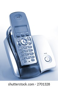 Modern wireless phone in cradle over blue background