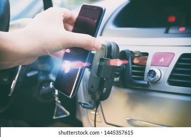 Modern wireless smartphone charging in a car with a hand putting a phone on it. Dashboard in background.