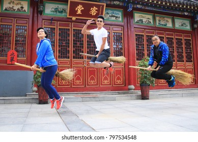 Modern witches flying, Friends having fun jumping and riding on bamboo broom, looks like witches riding on bamboo stick. Photo taken on 30 Jun 2017, in Inner mongolia.