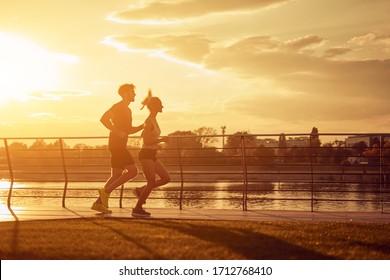 現代の女性と男性が、川の近くの都市の環境でジョギング/運動をしている。