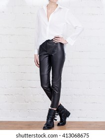 Modern woman outfit with white shirt and leather pants