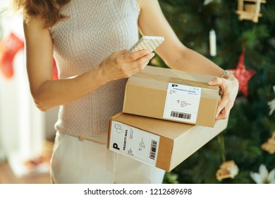 modern woman with parcels and smartphone using app near Christmas tree