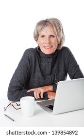 Modern woman pensioner using a laptop sitting at her desk thinking with a cup of coffee and her reading glasses alongside