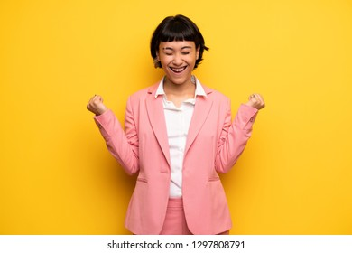 Modern woman with pink business suit shouting to the front with mouth wide open
