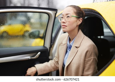 Modern woman in stylish clothes getting out of car