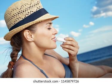 modern woman in swimwear on the seashore applying sun protection lipstick