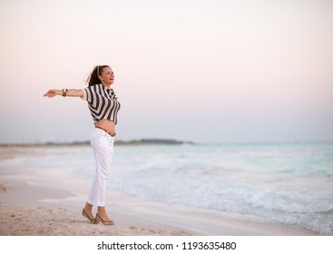 modern woman in white pants and striped shirt on the beach at sunset rejoicing
