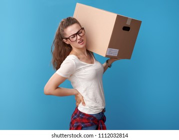modern woman in white shirt with a cardboard box having backache against blue background