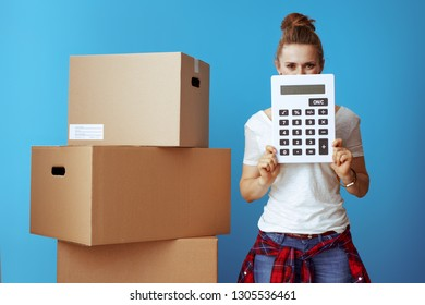 modern woman in white t-shirt near cardboard box hiding behind calculator isolated on blue background. Moving on budget.