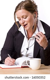 Modern woman writing in notebook with a satisfied expression and handsfree earplug.