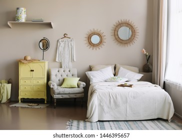 Modern woman's bedroom interior with wide bed, white linen, cushions and blanket, drawer cabinet, soft stool and a rug. Real photo
