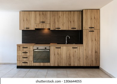 Modern wood kitchen in the apartment with white walls. Warm and copy space