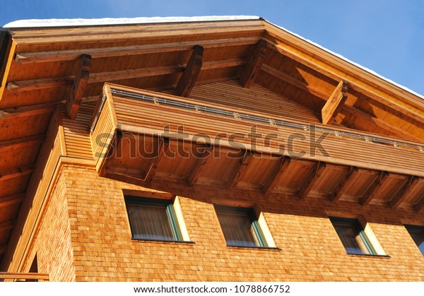Modern wooden alpine Style Architecture with Balcony and varnished wooden Slats, shingles and Timbers