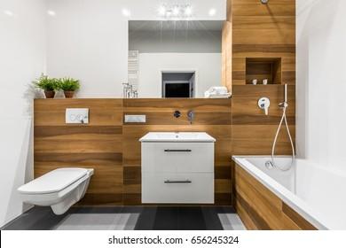 Modern, wooden bathroom with bathtub, mirror, toilet, cabinet and sink