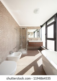 Modern wooden bathroom with large windows. Nobody inside