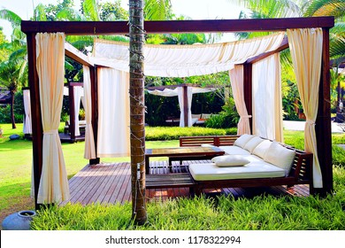 Modern wooden beach pergola  with withe curtain ,table, in front of the beach