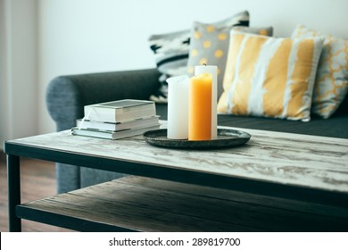 Modern wooden coffee table and cozy sofa with pillows. Living room interior and home decor concept. Toned image