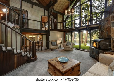 Modern wooden cottage house interior with living room close up. Gorgeous fireplace with natural stone tile trim and large glass wall. Northwest, USA