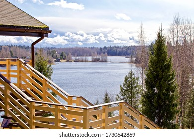Modern wooden hilltop house with panoramic lake views. Chalet on top of a hill among fir trees with beautiful views. Expensive suburban real estate. Wooden Cottage in a coniferous forest by the lake.