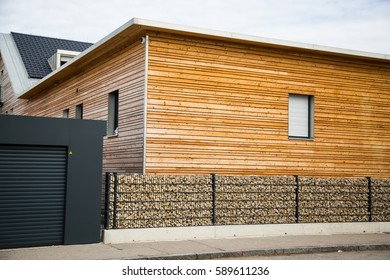 Modern wooden house with stone fence in front