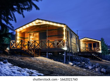 Modern wooden houses decorated with yellow glowing bulbs at the mountain resort