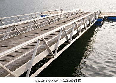 Modern wooden jetty or pier with metal sides without people or boats. Boat ramp and pier