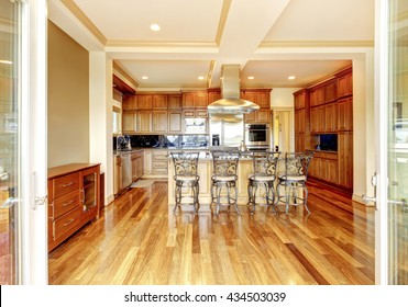 Modern wooden kitchen room design with hardwood floor, kitchen island, metal bar stools, trimmed ceiling and green walls.