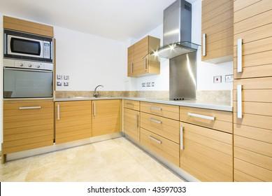 Modern wooden kitchen with silver appliances
