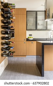 Modern wooden kitchen with wine racks and fitted cabinets