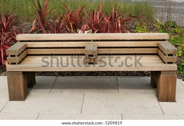 Modern wooden oak bench of minimalist style standing on a paved area.