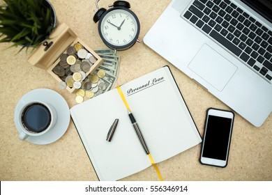 Modern wooden office desk table with laptop,smartphone, box of coins, paper money, table clock and cup of coffee. Writing PERSONAL LOAN on notebook page. Top view,flat lay.