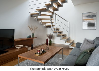 Modern wooden stairs with silver railing in small and stylish living room with wooden furniture, tv and gray sofa