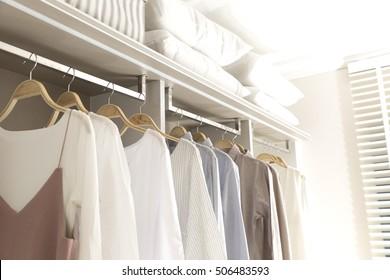 modern wooden wardrobe with clothes hanging on rail in walk in closet design interior