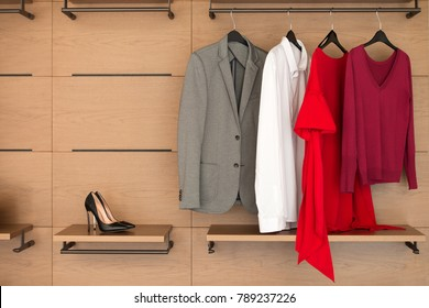 Modern wooden wardrobe with clothes and shoes hanging on rail