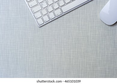 Modern working place with keyboard and mouse on gray wooden desk