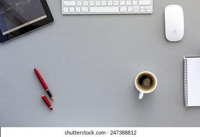 Local de trabalho moderno em mesa de madeira cinza. De cima vista sobre o local de trabalho bem equipado com tablet PC, mouse e teclado do computador, caneta vermelha, xícara de café fresco e bloco de notas em branco