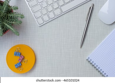 Modern working place with pen, keyboard, mouse, plant, and notepad on gray wooden desk
