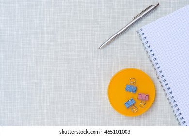 Modern working place with pen and notepad on gray wooden desk