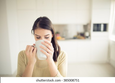 Modern working woman lifestyle-drinking coffee in the morning in the kitchen,starting your day.Positive energy and emotion.Productivity,happiness,enjoyment,determination.Morning ritual