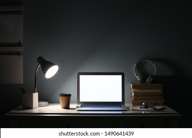 Modern workplace with laptop in evening