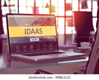 Modern Workplace with Laptop showing Landing Page with IDAAS - Identity as Service - Concept. Toned Image with Selective Focus. 3D Render.