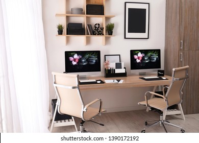Modern workplace with large desk and computers in room. Stylish interior