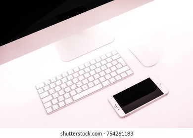 Modern workplace with metallic pc with keyboard and mouse, mobile phone, metalic laptop lying on a desk isolated on white background.