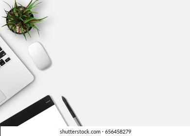 Modern workplace with notebook, little tree, gracphic tablet and graphic pen copy space on gray background. Top view. Flat lay style.