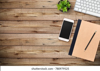 Modern workplace with smartphone and keyboard copy space on wood background. Top view. Flat lay style.