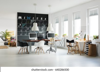 Modern workspace with blackboard calendar, desk, chairs and computers